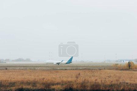Photo pour Avion atterrissant sur piste de l'aéroport avec ciel nuageux en arrière-plan - image libre de droit