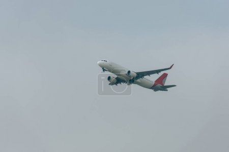 Photo pour Vue à faible angle de l'avion à réaction dans un ciel nuageux - image libre de droit