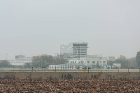 Photo for Airfield with runway and airport buildings with cloudy sky at background - Royalty Free Image
