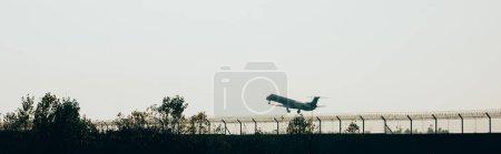 Photo pour Panoramic shot of airplane departure at sunset - image libre de droit