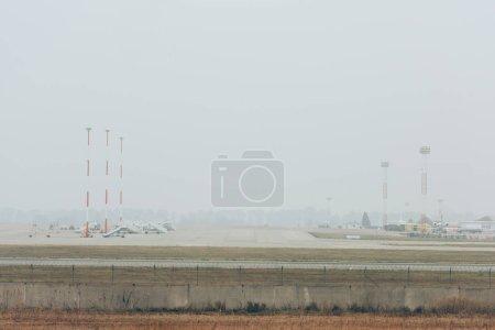 Photo pour Avions sur piste de l'aéroport avec ciel nuageux en arrière-plan - image libre de droit