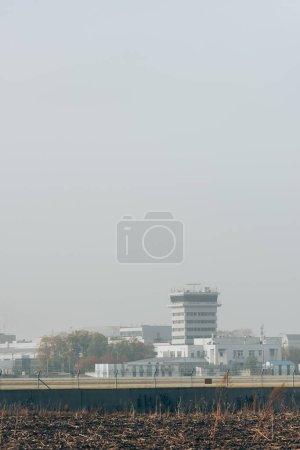 Photo pour Immeubles de l'aéroport avec piste d'atterrissage et ciel nuageux - image libre de droit
