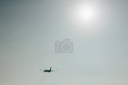 Silhouette of airplane in sky with sun