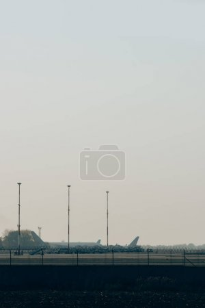 Photo for Aeroplanes on airport highway with sunset sky at background - Royalty Free Image