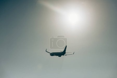 Low angle view of jet plane in sky with sun