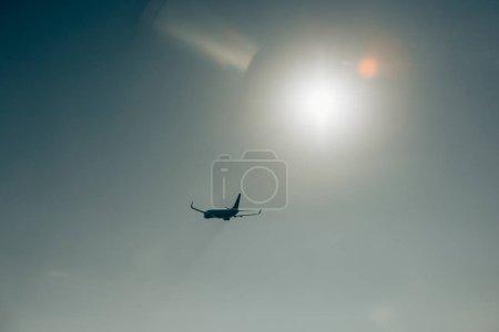 Photo pour Silhouette d'avion à réaction avec soleil dans un ciel clair - image libre de droit