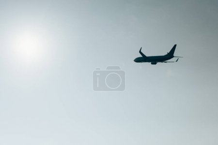 Photo pour Low angle view of silhouette of jet plane with sun in clear sky - image libre de droit