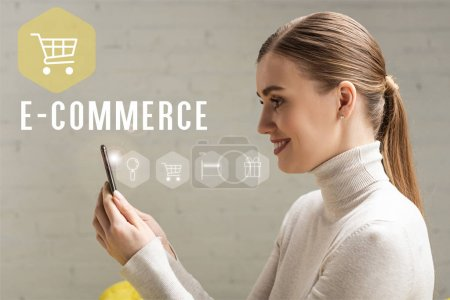 Photo for Side view of beautiful smiling girl holding smartphone, e-commerce concept - Royalty Free Image