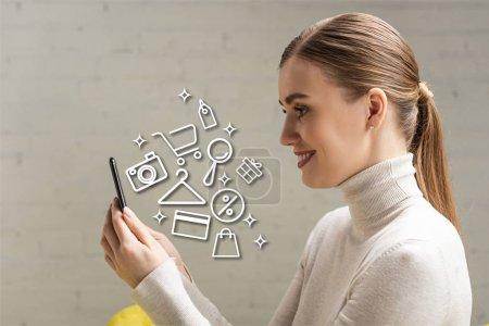 Foto de Vista lateral de la bella chica sonriente mirando al teléfono inteligente cerca de la ilustración. - Imagen libre de derechos