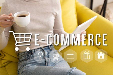 Cropped view of woman drinking coffee and holding digital tablet on couch, e-commerce concept