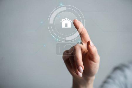 Photo pour Vue recadrée de la femme pointant du doigt sur la maison isolée sur gris - image libre de droit