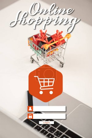 Laptop with credit card and toy gifts in cart on table, online shopping concept