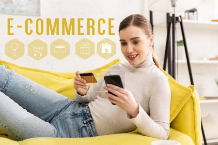 Photo for Smiling girl using smartphone and holding credit card on sofa in living room, e-commerce concept - Royalty Free Image