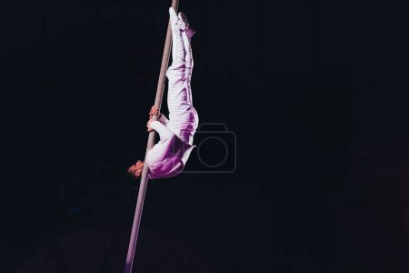 Photo for KYIV, UKRAINE - NOVEMBER 1, 2019: Side view of flexible air gymnast performing with pole in circus isolated on black - Royalty Free Image