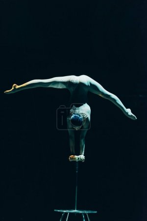 Photo for KYIV, UKRAINE - NOVEMBER 1, 2019: Back view of acrobat balancing on hands and doing split in circus isolated on black - Royalty Free Image