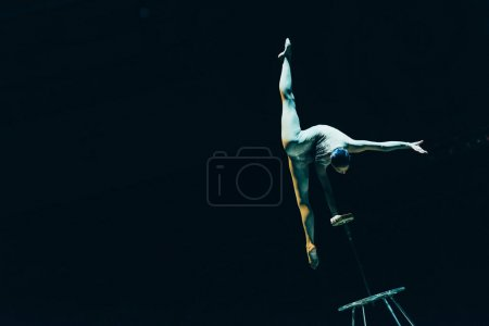 Photo for KYIV, UKRAINE - NOVEMBER 1, 2019: Gymnast doing split and handstand in circus isolated on black - Royalty Free Image