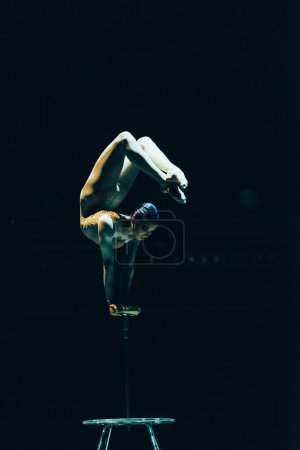 Photo for KYIV, UKRAINE - NOVEMBER 1, 2019: Female acrobat performing exercise in circus isolated on black - Royalty Free Image