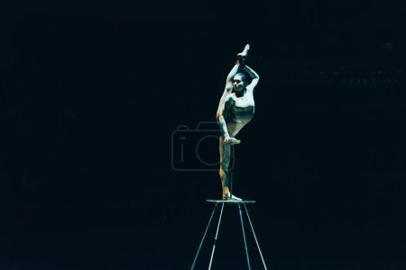 Photo for KYIV, UKRAINE - NOVEMBER 1, 2019: Flexible gymnast doing split while standing on equipment in circus isolated on black - Royalty Free Image