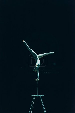 Photo for KYIV, UKRAINE - NOVEMBER 1, 2019: Gymnast performing handstand in circus isolated on black - Royalty Free Image