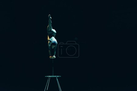 Photo for KYIV, UKRAINE - NOVEMBER 1, 2019: Back view of flexible acrobat balancing on hands in circus isolated on black - Royalty Free Image