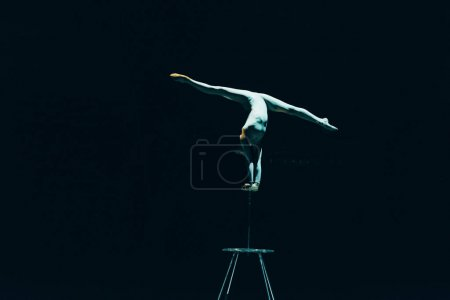 Photo for KYIV, UKRAINE - NOVEMBER 1, 2019: Female gymnast performing handstand and split in circus isolated on black - Royalty Free Image