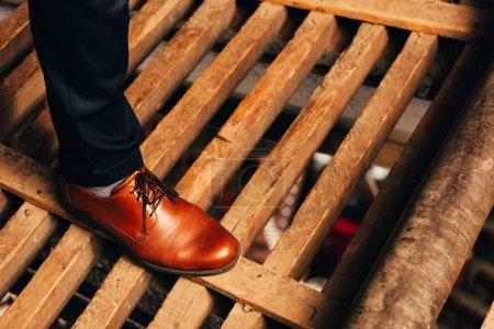 Ausgeschnittene Ansicht eines Mannes in braunem Schuh, der auf Holzplanken steht