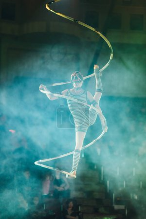 Photo for KYIV, UKRAINE - NOVEMBER 1, 2019: Back view of air gymnast performing in smoke in circus - Royalty Free Image
