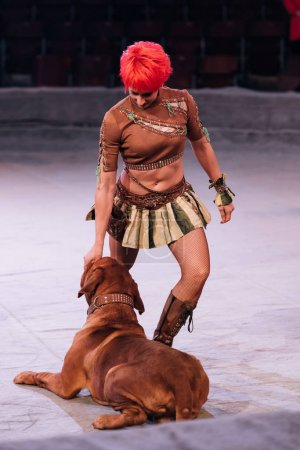 Photo for KYIV, UKRAINE - NOVEMBER 1, 2019: Attractive handler performing with dogue de bordeaux in circus - Royalty Free Image