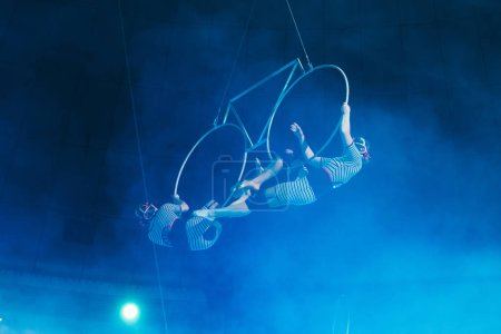 Foto de Kyiv, Ucrania - 1 de noviembre de 2019: Vista de bajo ángulo de gimnastas de aire en humo actuando con anillos en circo. - Imagen libre de derechos
