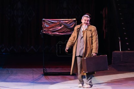 KYIV, UKRAINE - NOVEMBER 1, 2019:  Smiling artist with suitcase performing in circus