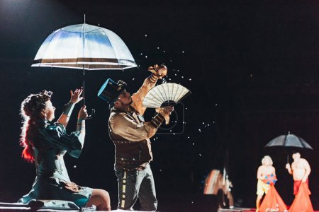 KYIV, UKRAINE - NOVEMBER 1, 2019: Selective focus of artists performing with umbrella, fan and and confetti in circus