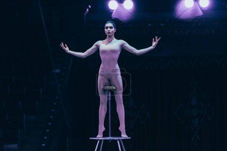 Photo pour KYIV, UKRAINE - 1er NOVEMBRE 2019 : Gymnaste attrayant dans un cirque avec projecteurs en arrière-plan - image libre de droit