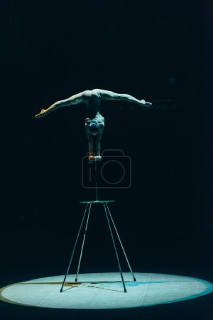 Photo for KYIV, UKRAINE - NOVEMBER 1, 2019: Back view of gymnast performing handstand and split in circus isolated on black - Royalty Free Image