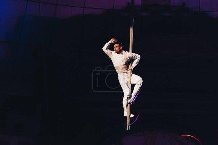 Photo pour KYIV, UKRAINE - 1er NOVEMBRE 2019 : Beau gymnaste aérien en pole position face à un cirque isolé en noir - image libre de droit