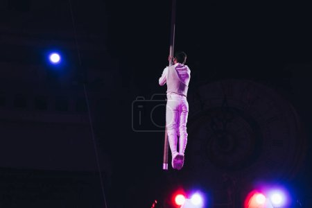 Photo for KYIV, UKRAINE - NOVEMBER 1, 2019: Back view of air gymnast with pole and light of floodlights in circus isolated on black - Royalty Free Image