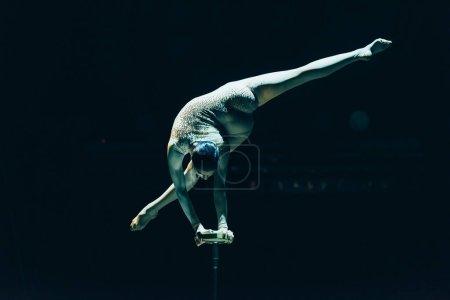 Photo pour KYIV, UKRAINE - 1er NOVEMBRE 2019 : Vue arrière du gymnaste flexible performant et divisé en cirque isolé sur noir - image libre de droit