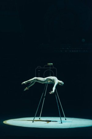 Photo for KYIV, UKRAINE - NOVEMBER 1, 2019: Side view of beautiful gymnast lying in spotlight in circus isolated on black - Royalty Free Image
