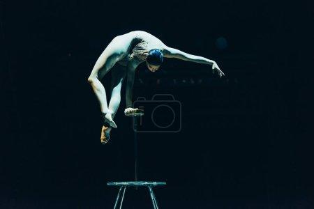 Photo pour KYIV, UKRAINE - 1er NOVEMBRE 2019 : acrobate féminine en équilibre dans un cirque isolé sur noir - image libre de droit