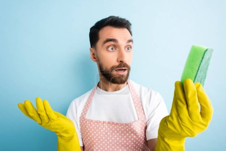Photo for Selective focus of surprised man in dotted apron looking at sponge on blue - Royalty Free Image