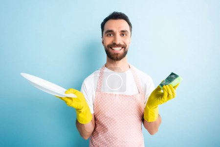 cheerful man in dotted apron holding plate and sponge on blue