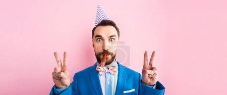 Photo pour Coup panoramique de l'homme d'affaires dans le ventilateur de partie de tenue de chapeau de partie dans la bouche et montrant le signe de paix isolé sur rose - image libre de droit