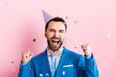 Photo pour Un homme d'affaires excité en chapeau de parti célébrant le triomphe près de tomber confetti sur rose - image libre de droit