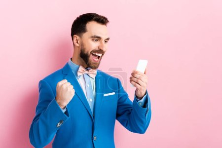 Photo for Excited bearded businessman holding smartphone on pink - Royalty Free Image