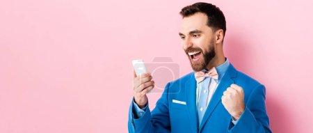 Photo pour Photo panoramique d'un homme d'affaires barbu excité tenant un smartphone en rose - image libre de droit