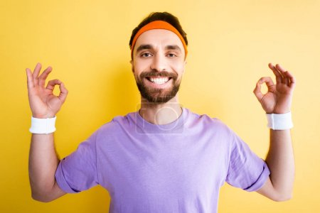 Photo for Cheerful sportsman showing ok sign on yellow - Royalty Free Image