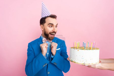Photo for Cropped view of businesswoman holding birthday cake near happy businessman isolated on pink - Royalty Free Image