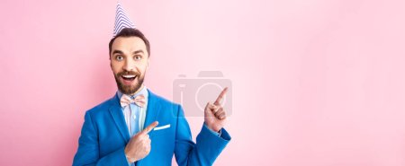 panoramic shot of happy businessman in party cap pointing with fingers isolated on pink