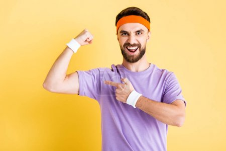 Photo for Excited man pointing with finger at muscle isolated on yellow - Royalty Free Image