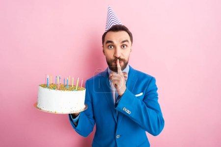 Photo pour Bel homme d'affaires arborant une somptueuse pancarte tout en tenant son gâteau d'anniversaire en rose - image libre de droit