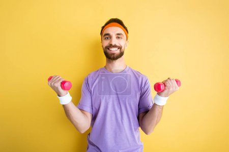 Photo for Positive sportsman exercising with pink dumbbells on yellow - Royalty Free Image